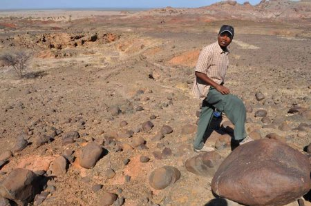 Timothy Ngundo, TBI fossil preparator, finds a massive basalt boulder outside the Namorutunga site at Lothagam.