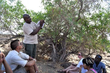 Dr. Fredrick Manthi lectures students in the field outside TBI camp.